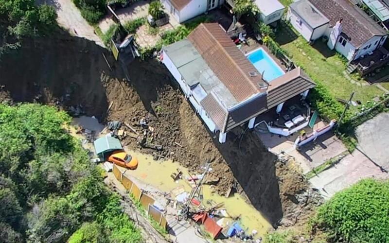 Ženě se znenadání propadla polovina domu. Fotce svého auta spadlého na pláži se ale s chutí zasmála.