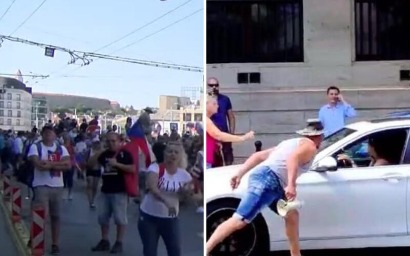 VIDEO: Žena hádzala vajcia po médiách, muži napadli kameramana a protestujúci búchali či pľuli na autá.