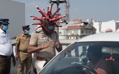 Straší koronavirovou přilbou lidi, aby zůstávali doma. Pokud vyjdeš ven, já vejdu dovnitř, upozorňuje indický policista.