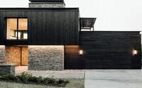Černý dřevěný obklad v kombinaci s kamenem na fasádě jako kontrast k modernímu interiéru, který obývá mladá rodina