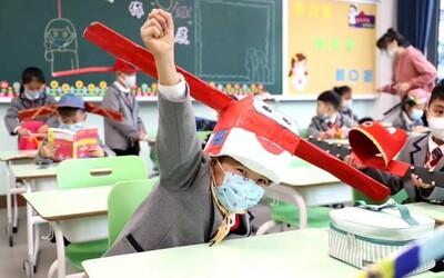 Čínski školáci sa vrátili do škôl v klobúkoch s metrovými tyčami na hlavách, aby sa nepribližovali jeden k druhému
