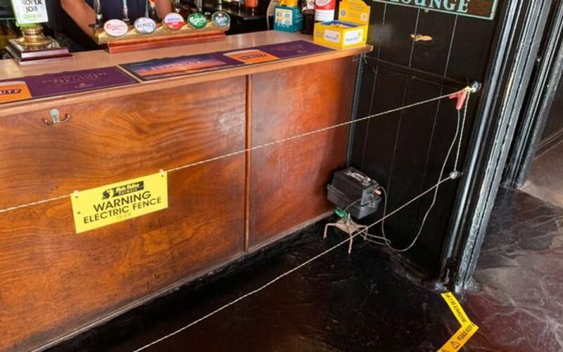 V britské hospodě nainstalovali před bar elektrický drát. Majitel chce donutit lidi udržovat dostatečný odstup.