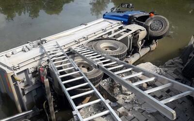 Nehoda v Poličce: Řidič nákladního vozu naboural tři auta a sjel do rybníku. Záchranářům se jej nepodařilo oživit.