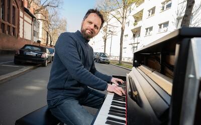 Hudebník vytáhl klavír ven a hraje pro své sousedy uprostřed ulice. I takto vypadá koronavirová krize