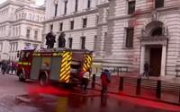 Londýnští aktivisté stříkali ve videu umělou krev na budovu, hadice se jim vymkla kontrole