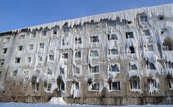 Ruský panelák obkolesil ľad. Voda z prasknutého potrubia zamrzla priamo na budove