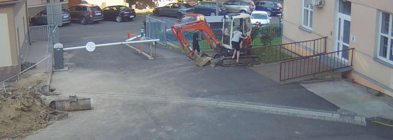 VIDEO: Mladík z Ústí nad Labem vlezl do zaparkovaného bagru a vyzkoušel si, jak se ovládá. Poničil fasádu školy